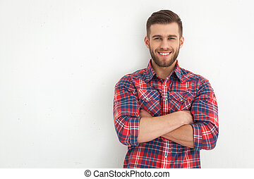 Handsome young guy standing against white wall.