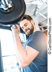 Handsome young guy workout with barbell