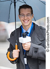 young journalist working outdoors in the rain
