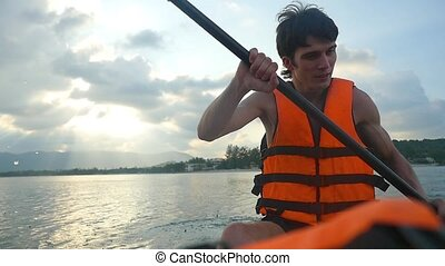 Handsome young kayaker paddling in the sea while has...