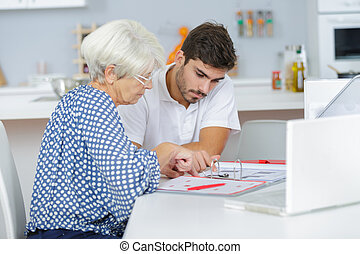 handsome young lad helping senior lady with her taxes