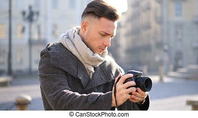 Handsome young male photographer filming video outdoor - ...