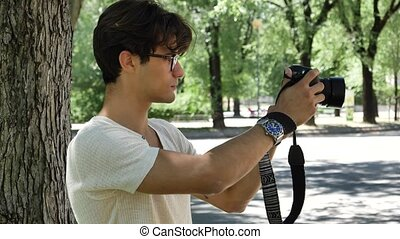 Handsome young male photographer taking photograph with...