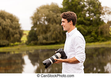 young male photographer with dslr camera outdoors