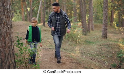 Handsome young man and his cute little son are walking in forest and talking enjoying fresh air, nature and communication. Family, fatherhood and autumn tourism concept.
