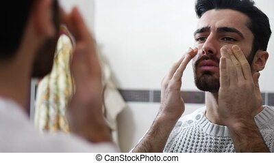 Handsome young man applying moisturizing cream on face in...
