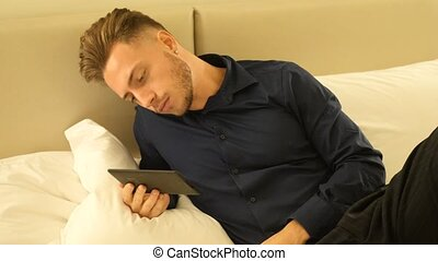 Handsome young man at home reading with ebook reader lying...