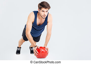 Handsome young man athlete doing push ups on red ball
