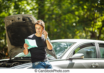 Handsome young man calling for assistance with his car...