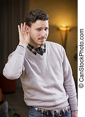 Handsome young man can't hear, putting hand around his ear....
