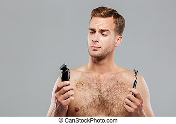 Handsome young man choosing razor over gray background