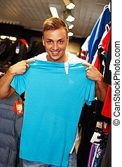 Handsome young man choosing t-shirt in a sport outlet