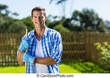 young man cleaning home garden