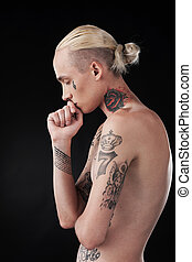 handsome young man closed eyes. tattooed blond male side...