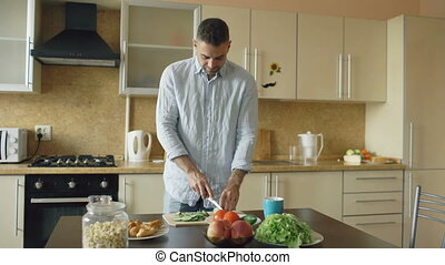 Handsome young man cooking vegetarian breakfast cutting vegetables for salad in kitchen at home