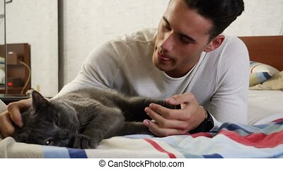 Handsome Young Man Cuddling his Gray Cat Pet - Handsome...