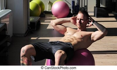 Handsome young man doing abs exercises on mat - Attractive...