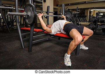 young man doing bench press workout in gym