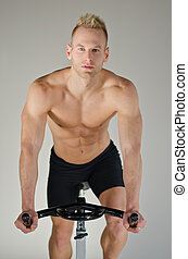 Handsome young man doing spinning on bike - Attractive young...