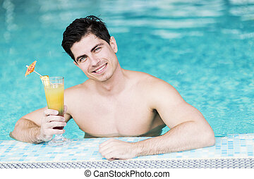 Handsome young man drinking a cocktail in the water