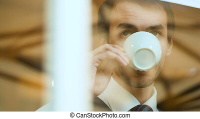 handsome young man drinks coffee