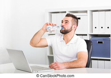 Handsome young man drinks water from a bottle