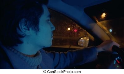 Handsome young man driving a car at night