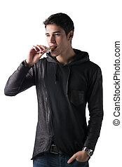 Handsome young man eating cereal bar, isolated