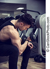 Handsome young man exercising biceps in gym