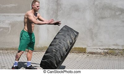 Handsome young man exercising flipping huge tire