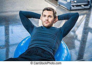 Handsome young man exercising on fitness ball at gym