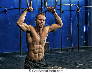 Handsome young man exercising with rings