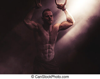 Handsome young man exercising with rings in gym