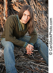 Handsome young man with long hair in an outdoor setting