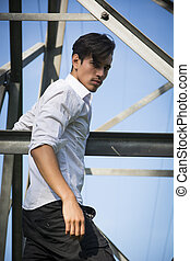 Handsome young man hanging from metal electricity trellis