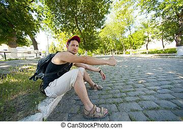 man hitchhiking along a road