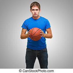 Handsome young man holding a basketball