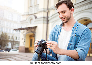 Handsome young man holding a camera
