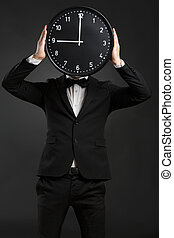 Handsome young man holding a clock
