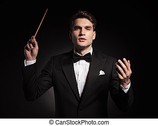 Handsome young man holding a stick in his hand, conducting...