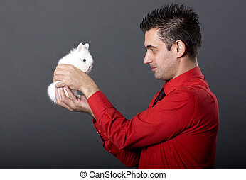 Handsome young man holding baby rab