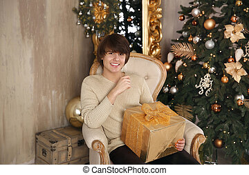 Handsome young man holding gift box sitting on armchair in beige interior. Happy smiling boy looking at camera.
