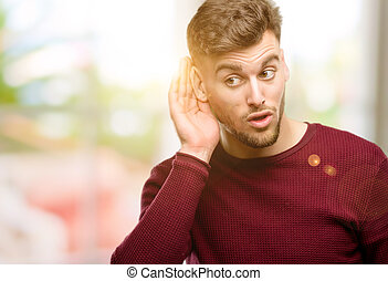 Handsome young man holding hand near ear trying to listen to interesting news expressing communication concept and gossip
