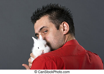 Handsome young man holding rabit