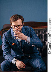 Handsome young man in a classic suit drinking red wine in...