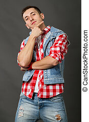 man in a denim vest on a gray background