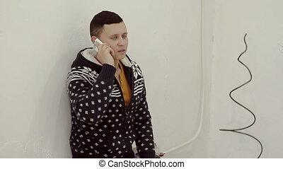 Handsome young man in a sweater talking on the phone