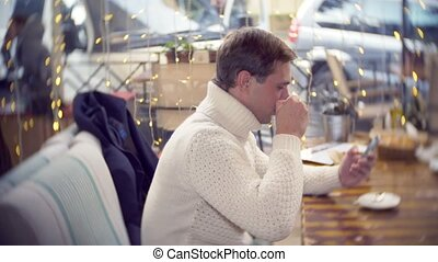 handsome young man in a white sweater using a smartphone, sitting in a cafe in the city on an against a window. background blur. 4k