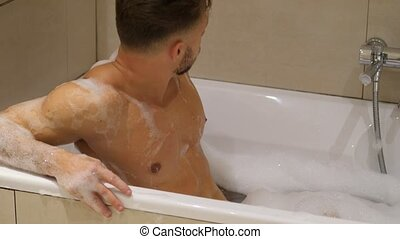 Handsome young man in bathtub at home having bath, leaning...