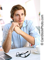 Handsome young man in blue office shirt thinking